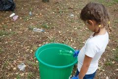 Detrás de la muchacha agradable con las coletas del peinado La bolsa de plástico que lanza en la papelera de reciclaje Tierra y d Fotos de archivo libres de regalías