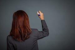 Detrás de la muchacha asiática del negocio escriba en el aire Foto de archivo libre de regalías