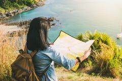 Detrás de la muchacha del viajero con la mochila que mira la dirección en mapa Imagenes de archivo