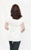 Detrás de la muchacha en una blusa blanca Imagen de archivo
