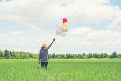 Detrás de la mujer asiática del inconformista joven con los globos coloreados en hierba fotos de archivo libres de regalías