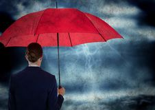 Detrás de la mujer de negocios con el paraguas adentro contra tormenta con la capa del grunge fotografía de archivo