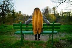 Detrás de la mujer del pelo rubio que se sienta en banco de parque imagen de archivo libre de regalías