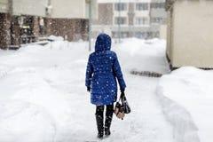 Detrás de la mujer en chaqueta del amanecer que camina a través de la calle de la ciudad durante las nevadas pesadas y ventisca e foto de archivo