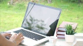 Detrás de la mujer joven que mecanografía en el ordenador portátil Imagenes de archivo