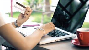 Detrás de la mujer joven que mecanografía en el ordenador portátil y la tarjeta de crédito para el shopp Imagen de archivo