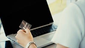 Detrás de la mujer joven que mecanografía en el ordenador portátil y la tarjeta de crédito para el shopp Fotos de archivo