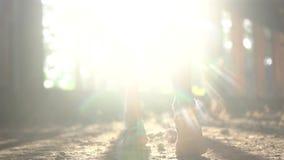 Detrás de la mujer que camina en el edificio abandonado a través de rayos de la luz del sol almacen de metraje de vídeo