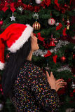 Detrás de la mujer que desea en el árbol de navidad Imagenes de archivo