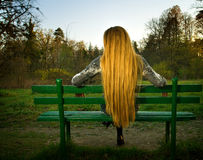 Detrás de la mujer que se sienta solamente en banco de parque imagenes de archivo