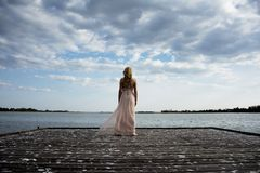 Detrás de la mujer rubia en la presentación del vestido de noche Imagenes de archivo