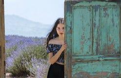 Detrás de la puerta de madera vieja, la chica joven fotos de archivo libres de regalías