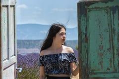 Detrás de la puerta de madera vieja, la chica joven imagen de archivo