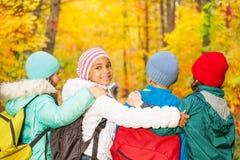 Detrás de niños con las mochilas que se colocan en cierre de la fila Imágenes de archivo libres de regalías