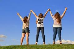 Detrás de tres muchachas que llevan a cabo las manos en la hierba Foto de archivo libre de regalías