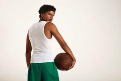 Detrás de un atleta negro muscular que lleva a cabo el baloncesto de cuero Fotografía de archivo libre de regalías