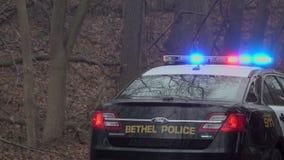 Detrás de un coche policía cerca de una emergencia metrajes