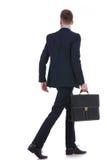Detrás de un hombre de negocios con la maleta que se va Imágenes de archivo libres de regalías