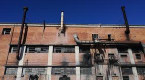 Detrás de una fábrica vieja con los tubos imágenes de archivo libres de regalías