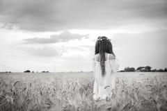 Detrás de una muchacha hermosa en un campo de trigo con el pelo largo y una guirnalda fotografía de archivo libre de regalías
