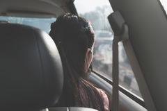 Detrás de viaje de la muchacha a lo largo del camino y mirando a través de ventana dentro del coche Imagen de archivo libre de regalías