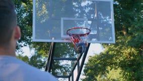 Detrás del baloncesto de salto y que lanza del hombre, la bola golpea el anillo, pasando a través del aro, jugando en parque, d3i almacen de metraje de vídeo