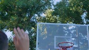 Detrás del baloncesto que lanza del hombre joven y del anillo que falta, fall del jugador para golpear la bola en el aro, jugando metrajes
