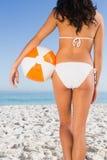 Detrás del cuerpo perfecto de la mujer que sostiene la pelota de playa Fotografía de archivo
