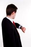 detrás del hombre de negocios joven que mira en su reloj Fotos de archivo libres de regalías