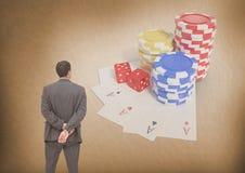 Detrás del hombre que mira las fichas de póker y los naipes del casino Imagen de archivo