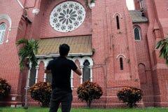 Detrás del hombre que se coloca delante del edificio principal de la iglesia y de la torre de iglesia en la catedral de la trinid Fotografía de archivo