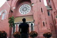 Detrás del hombre que se coloca delante del edificio principal de la iglesia y de la torre de iglesia en la catedral de la trinid Foto de archivo libre de regalías