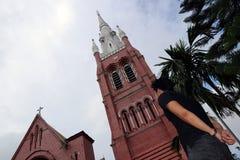 Detrás del hombre que se coloca delante del edificio principal de la iglesia y de la torre de iglesia en la catedral de la trinid Fotos de archivo