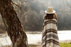 Detrás del inconformista de la mujer el sombrero y el poncho que llevan en el árbol cerca rive fotografía de archivo libre de regalías