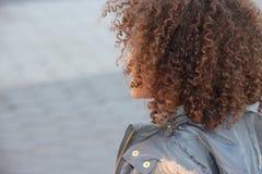 Detrás del jefe rizado del pelo de la muchacha Imagen de archivo