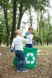 Detrás del muchacho justo con las coletas del peinado La bolsa de plástico que lanza en la papelera de reciclaje Tierra y desperd Fotografía de archivo libre de regalías