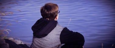 Detrás del muchacho que se sienta por un lago imágenes de archivo libres de regalías
