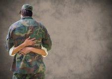 Detrás del soldado que abrazaba con grunge cubrió contra fondo marrón imagenes de archivo
