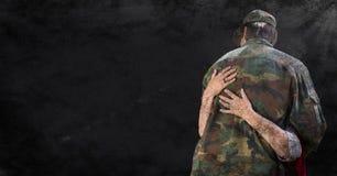 Detrás del soldado que es abrazado contra fondo negro del grunge con la capa y la llamarada Imagen de archivo