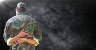 Detrás del soldado que es abrazado contra fondo negro del grunge con la llamarada foto de archivo libre de regalías