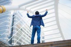 Detrás del soporte asiático del hombre de negocios y de aumentar para arriba sus manos celebró el suyo acertado en carrera y la m imagenes de archivo