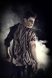 Detrás del zombi masculino que se coloca en negro, dando vuelta alrededor Imagenes de archivo