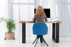 detrás opinión la empresaria que trabaja en el lugar de trabajo con la pantalla de ordenador fotografía de archivo