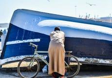Detrás-vista de una persona que lleva el vestido largo que se inclina sobre la bicicleta y que habla con otra persona, Marruecos imagen de archivo