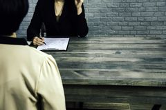 Detrás vista posterior - la hembra presenta solicitudes de trabajo a los encargados y a los comités, departamentos del reclutamie imagen de archivo