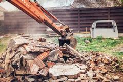 Detriti, pietra e calcestruzzo resistenti di demolizione di caricamento del bulldozer dell'escavatore a cucchiaia rovescia per ri Fotografie Stock Libere da Diritti