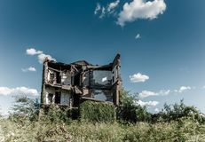 Detroit city center scene. Ruins of an old residential house overgrown by weeds and trees in Detroit city, Michigan stock photo