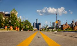 Detroit city street. An empty street through an old Detroit city neighborhood with downtown buildings in the background stock image