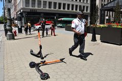 Detroit Spin scooters on sidewalk. DETROIT, MI / USA - JUNE 30, 2019:  People walk past Spin scooters on a sidewalk in downtown Detroit stock images