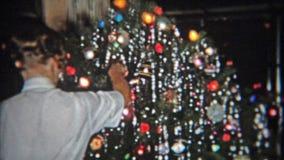 DETROIT, MICHIGAN 1953: Adolescente que presenta delante de escena de la natividad del árbol de navidad almacen de metraje de vídeo